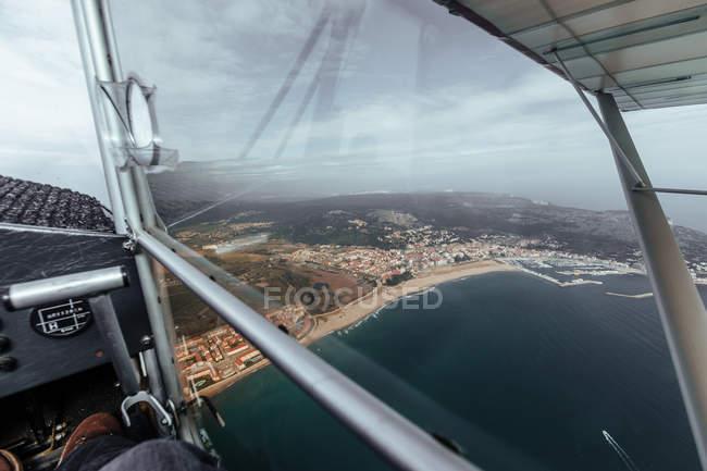 Vista aérea de la costa del mar desde el interior de una cabina de un pequeño avión - foto de stock