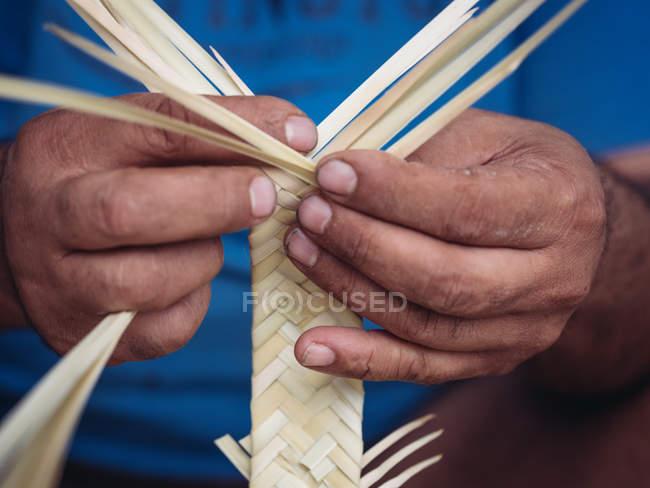 Mãos de artesão anônimo usando gancho para tecer folhas de palma secas de fibra enquanto trabalhava na oficina — Fotografia de Stock