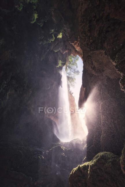 Vista de dentro da caverna selvagem com feixe cintilante de luz solar contra a entrada — Fotografia de Stock