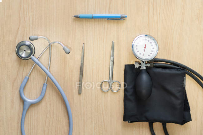Медицинский стетоскоп рядом с тонометром, ножницами, пинцетом и ручкой на деревянном столе — стоковое фото
