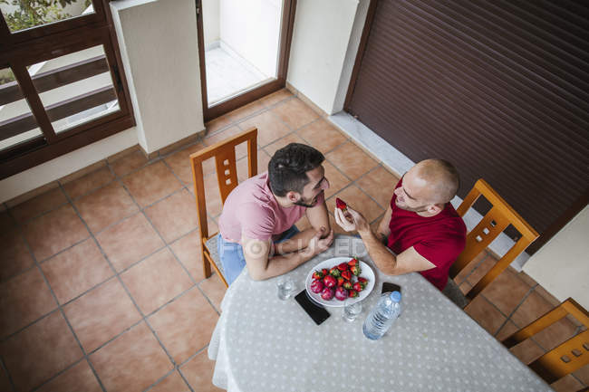 Cheerful gay couple eating strawberries at table in kitchen — Stock Photo