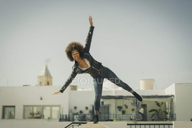 Pretty African American female in stylish outfit balancing on building wall against cloudless sky — Stock Photo
