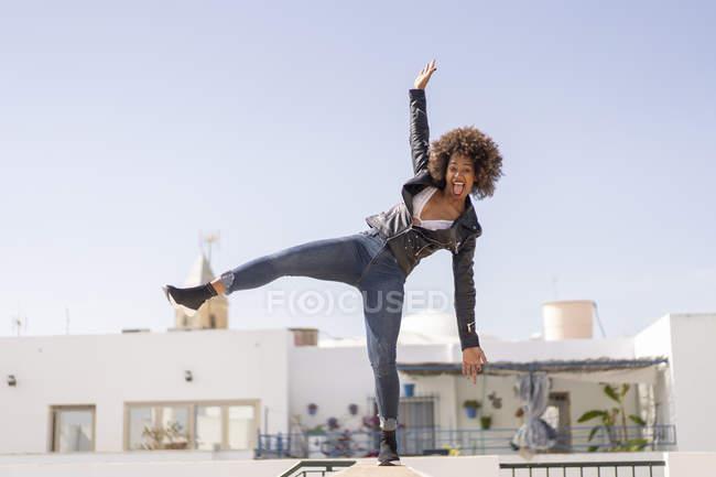 Hübsche Afroamerikanerin balanciert in stylischem Outfit auf Hauswand gegen wolkenlosen Himmel — Stockfoto