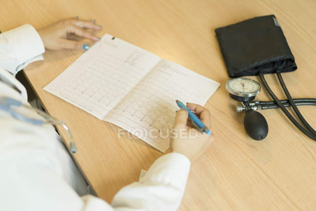 Close-up of female doctor in uniform writing on paper while sitting at table with tonometer — Stock Photo