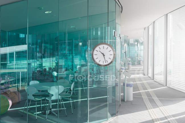 Дизайн сучасного офісу з блакитними прозорими стінами і легким передпокою з годинником, Швейцарія — стокове фото