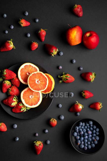 Várias frutas frescas e bagas espalhadas no fundo preto — Fotografia de Stock