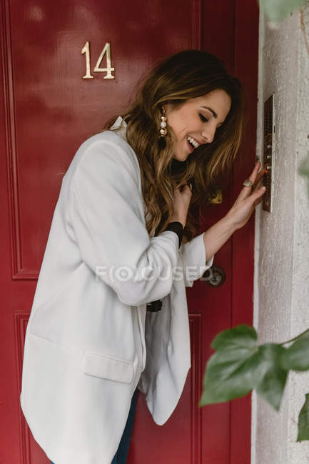 Stylish woman standing near red door and laughing — Stock Photo