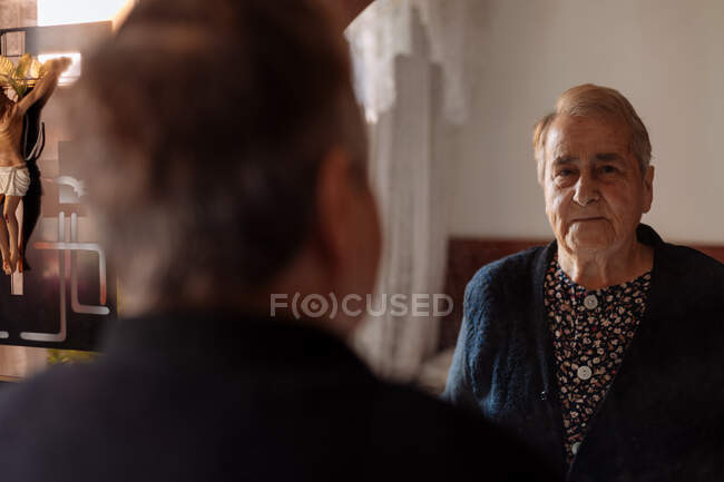 Elderly person looking in the mirror of his house — Stock Photo