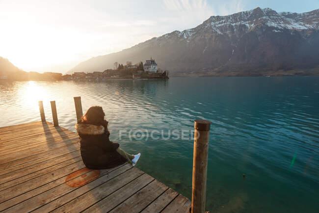 Назад вид жінка, сидячи на дереві Пірс над бірюзовим озером в снігових горах Швейцарії — стокове фото