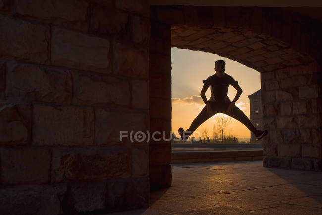 Unrecognizable teenager break dancing in arch at sunset — Stock Photo