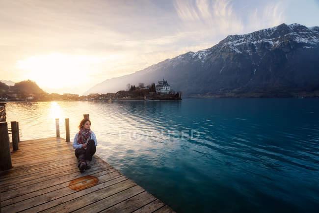 Женщина, сидящая на деревянном пирсе над бирюзовым озером в снежных горах Швейцарии — стоковое фото