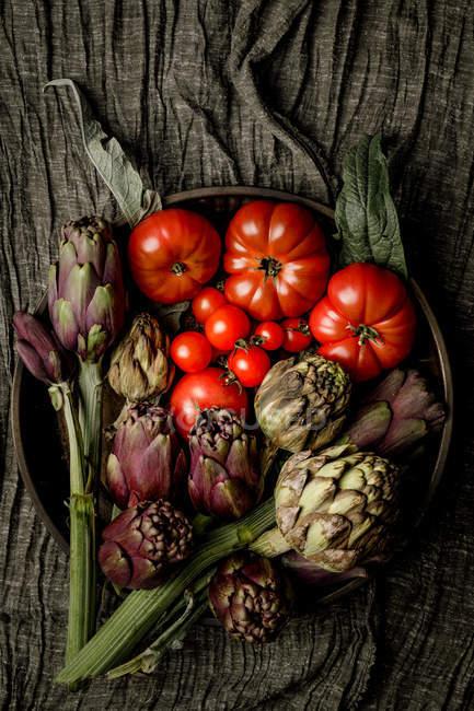Чаша различных свежих овощей и салфеток на деревенском столе на кухне — стоковое фото