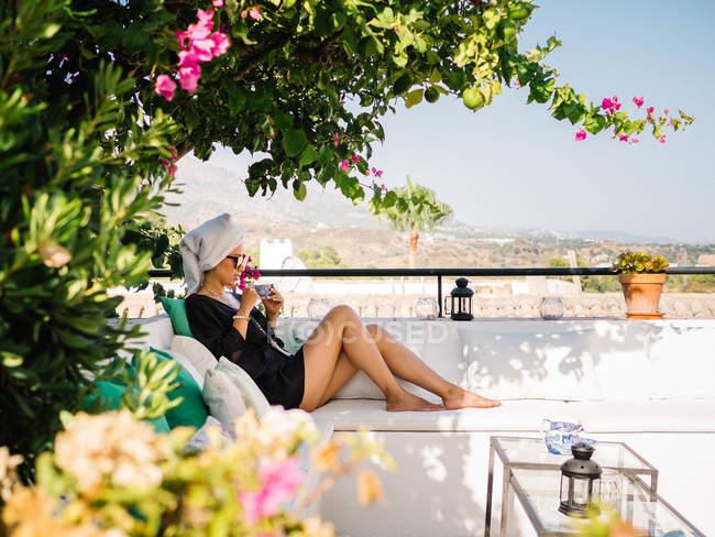 Жінка в чорній атласній сукні і рушник в голові відпочиває в балконі, насолоджуючись прекрасними краєвидами в сонячний яскравий ранок — стокове фото