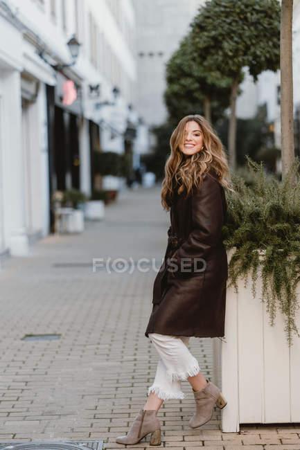 Élégant jeune femme en cuir vintage manteau posant sur la rue de la ville — Photo de stock