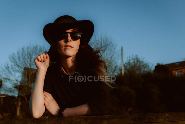 Pensive woman wearing trendy sunglasses with black hat leaning on hand in sunlight — Stock Photo
