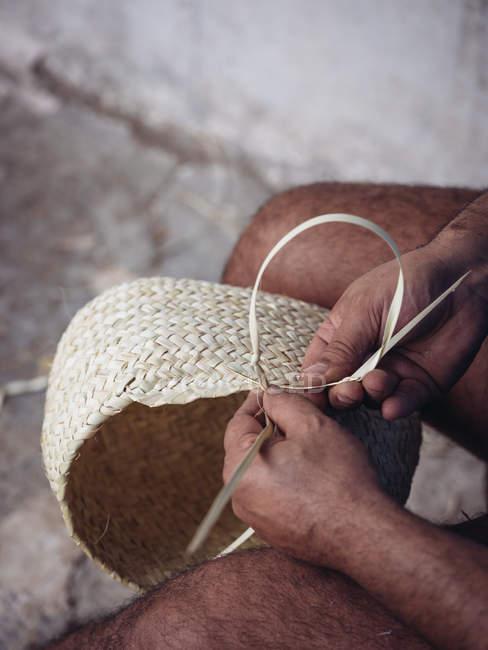 Manos de tejido artesanal anónimo encantadora cesta con fibra de palma seca trenzada - foto de stock