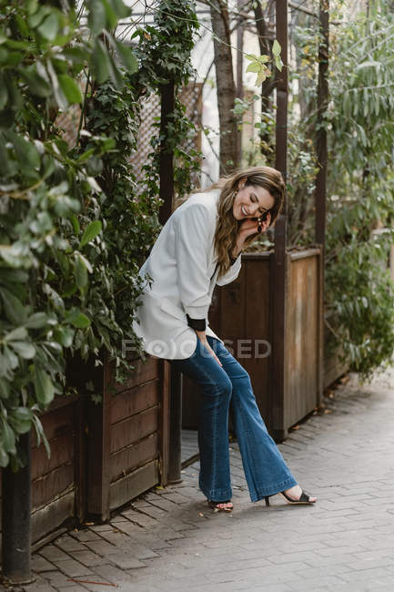 Stylish young woman sitting on planter in garden and laughing — Stock Photo