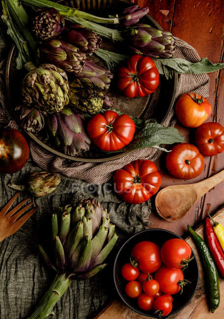 Ciotole di varie verdure fresche e tovaglioli di stoffa su tavolo rustico in cucina — Foto stock