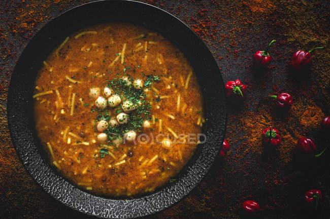Традиційні Harira суп для Рамадану в чорній мисці на темному тлі з червоним перцем — стокове фото