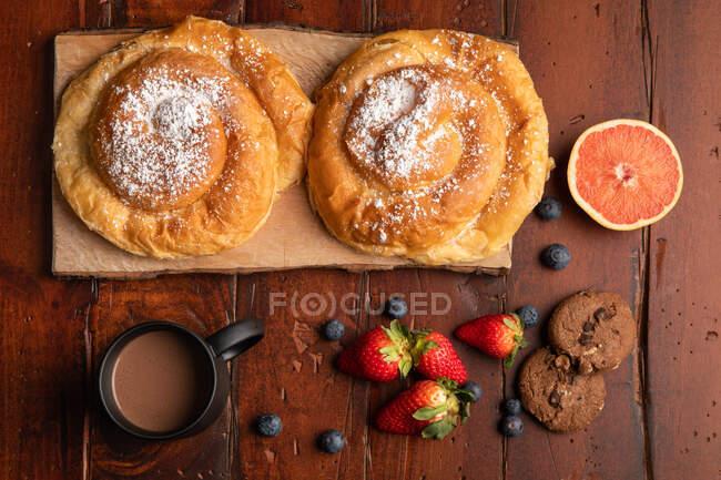 Bebida quente fresca e vários saborosos alimentos de pequeno-almoço colocados na mesa de madeira na parte da manhã — Fotografia de Stock