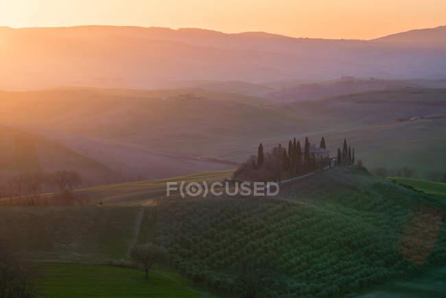 Paisagem pitoresca de campos verdes com casa de campo e árvores em luz brilhante do pôr do sol, Itália — Fotografia de Stock