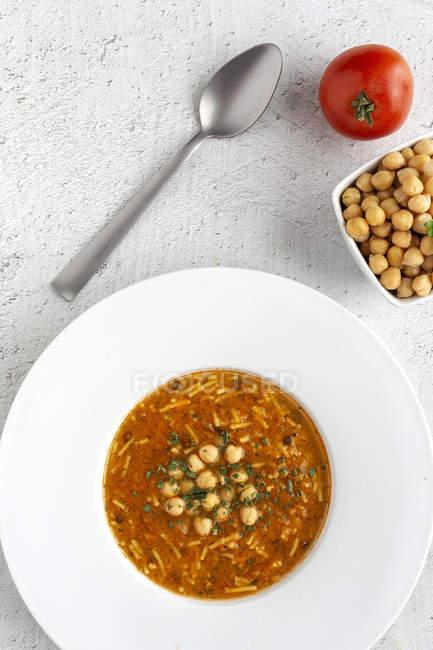 Soupe traditionnelle Harira pour Ramadan en assiette blanche avec cuillère et ingrédients — Photo de stock