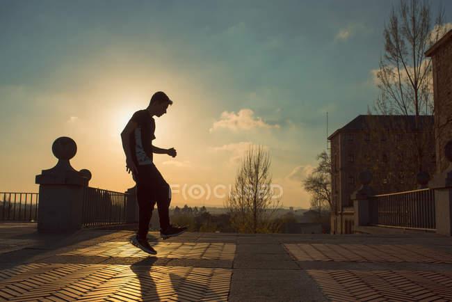 Teenager break dancing on street at sunset — Fotografia de Stock