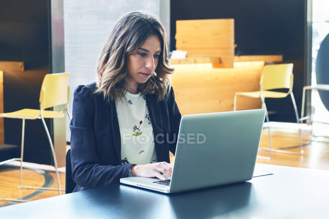 Woman sitting at table in a Coffee browsing laptop — Stock Photo