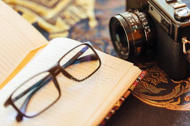 Close up do caderno aberto ao lado de uma câmera do vintage na tabela decorativa — Fotografia de Stock