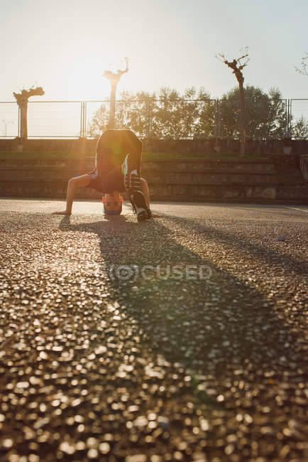 Teenager doing headstand while break dancing on sports ground — Stock Photo