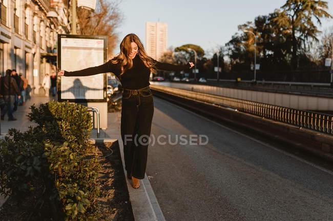Mulher elegante balanceamento na calçada perto da estação de metro — Fotografia de Stock