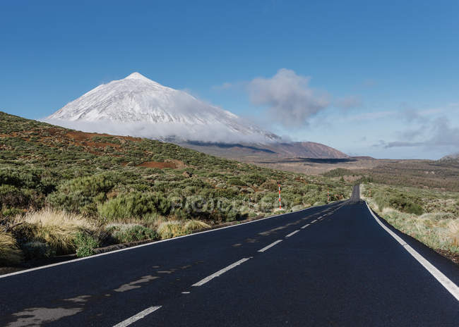 Asphalt countryside road through grassy terrain near magnificent snowy mountain peak on sunny day on Canary Islands, Spain — Stock Photo