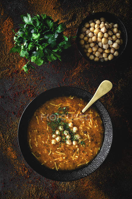 Traditionelle Harira-Suppe für Ramadan in schwarzer Schüssel auf dunklem Hintergrund mit Zutaten — Stockfoto