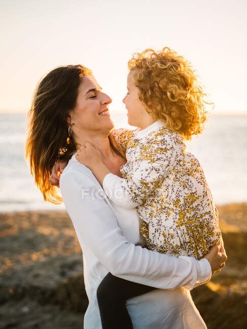 Middle aged woman with her daughter at sea shore smiling and hugging each other — Stock Photo