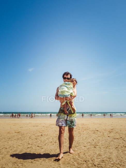 Милая сцена папа держит и обнимает свою маленькую дочь на пляже зимой — стоковое фото