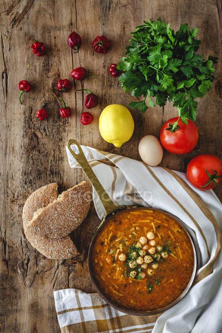Традиційний суп Harira для Рамадану в мисці на сільському дерев'яному столі з інгредієнтами — стокове фото