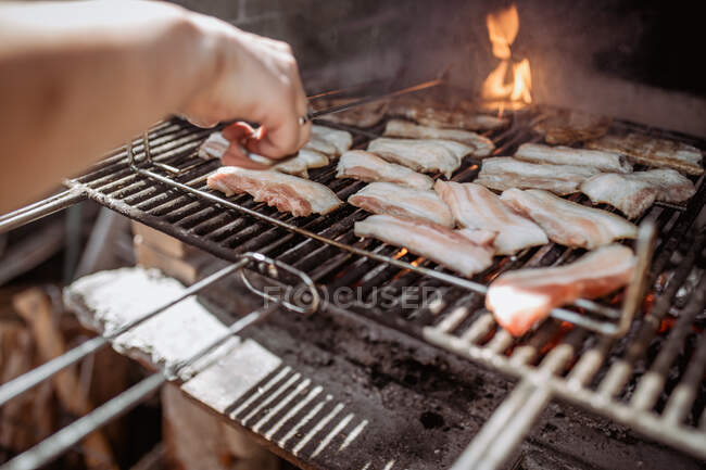 Crop person cooking bacon in barbecue — Stock Photo