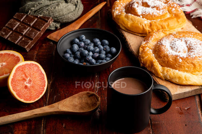 Maçã vermelha fresca e mirtilos maduros colocados em mesa de madeira perto de caneca de bebida quente aromática e pão delicioso para o café da manhã — Fotografia de Stock