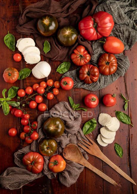 Frische Tomaten und Mozzarella mit Basilikumblättern für Salat auf Holzoberfläche und Stoffserviette — Stockfoto