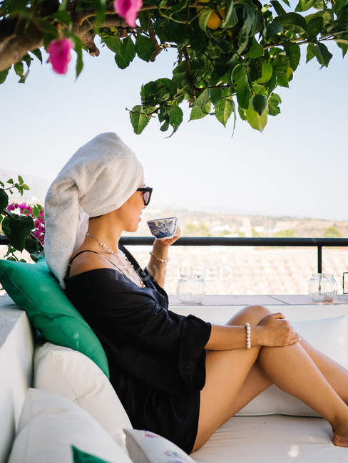 Woman in black satin dressing gown and towel in head resting in a balcony enjoying beautiful views on a sunny bright morning — Stock Photo
