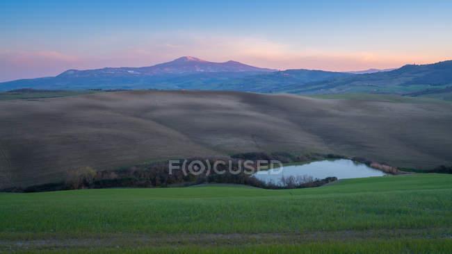 Majestätische Landschaft des grünen Tals mit Feldern, See und Bergkette bei Sonnenuntergang in der Toskana, Italien — Stockfoto