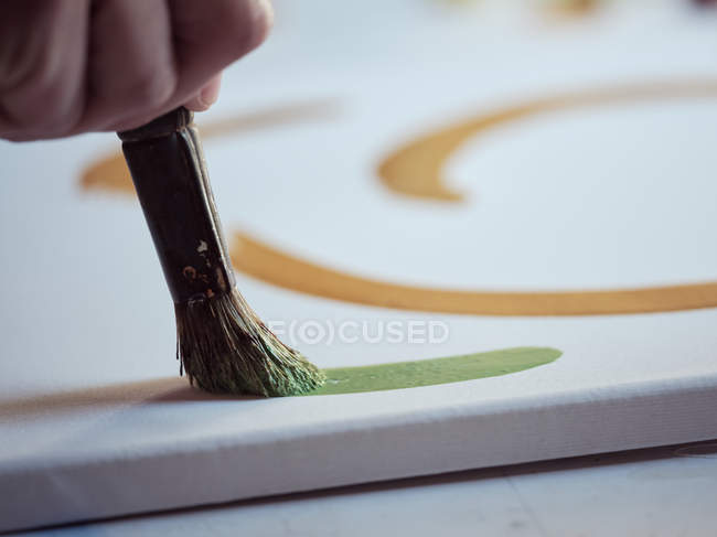 Closeup hand of anonymous artist with paintbrush and green paint drawing picture on canvas in studio — стокове фото