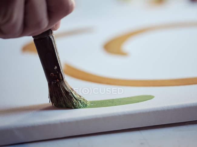 Фотографія крупним планом анонімний художник з пензлем і зеленою фарбою малюнок на полотні в студії — стокове фото