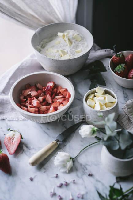 Vários ingredientes frescos para massa de morango saboroso colocado em mesa de mármore na cozinha — Fotografia de Stock