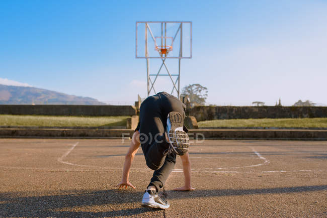 Unrecognizable teenager break dancing on sports ground — Stock Photo