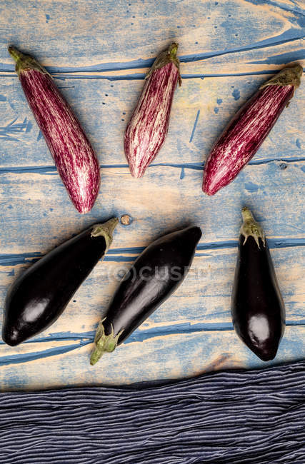 Set of fresh ripe purple and black eggplants near piece of striped cloth on weathered wooden tabletop — Stock Photo