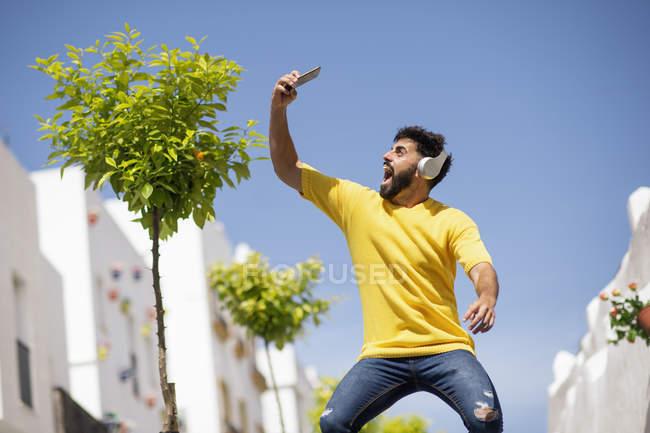Веселий бородатий чоловік в навушниках кричали і приймаючи селфі, стоячи на міській вулиці і слухати музику в сонячний день — стокове фото
