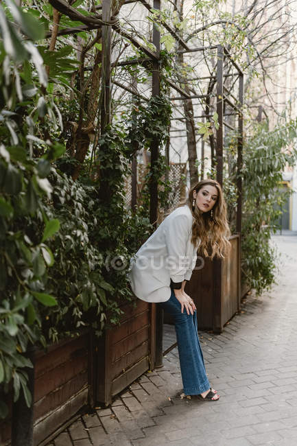 Stylish young woman sitting on planter in garden and looking away — Stock Photo