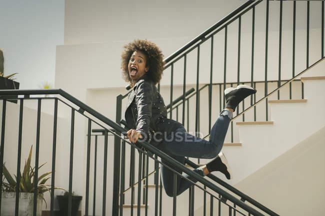 Возбужденных афро-американских женщин, глядя в камеру и кричать, опираясь на перила и прыжки на лестнице здания — стоковое фото