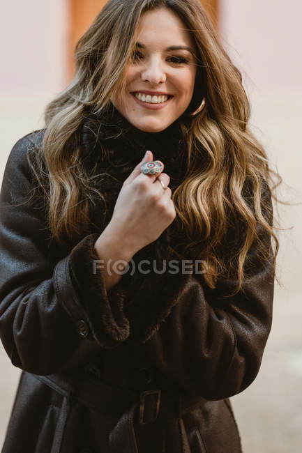 Stylish smiling young woman in vintage leather coat looking at camera — Stock Photo